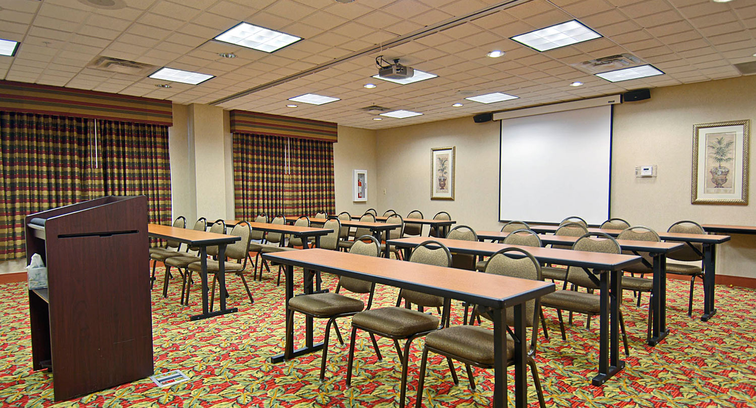 classroom style chairs and tables with a white projection screen pulled down
