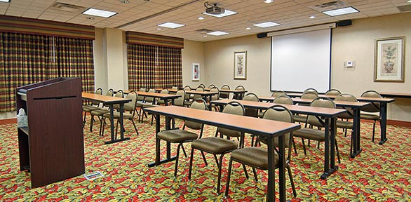 brown podium looking over classroom style layout in a meeting room
