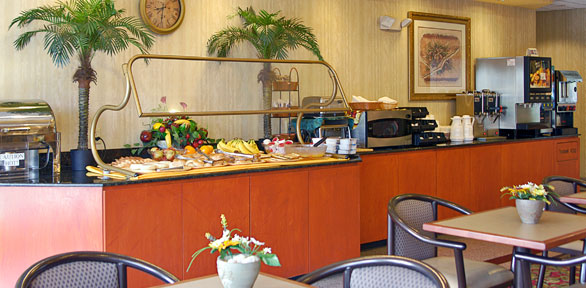 food buffet with fruits, cereal, hot drinks, cold drinks and sitting area