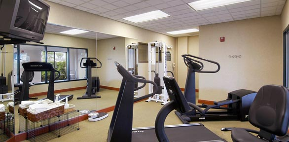 fitness center with treadmill, bikes, weight machine, large mirrors and TV