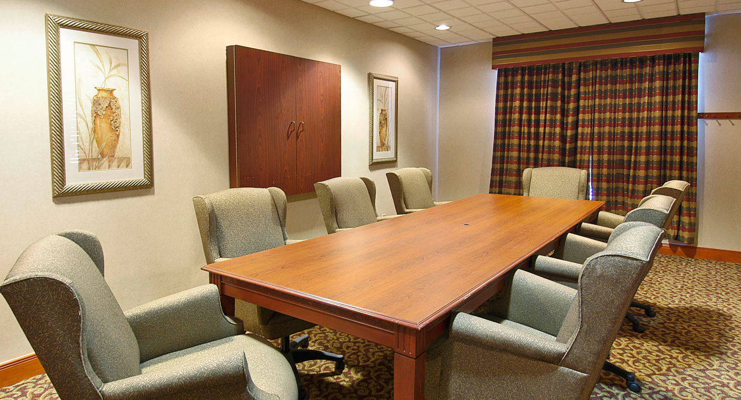 brown wood tv casing with a boardroom style layout in a meeting room