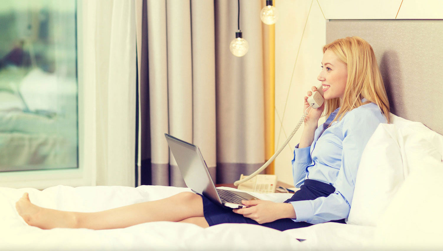 business lady in a skirt seating on the bed while making phone calls with laptop